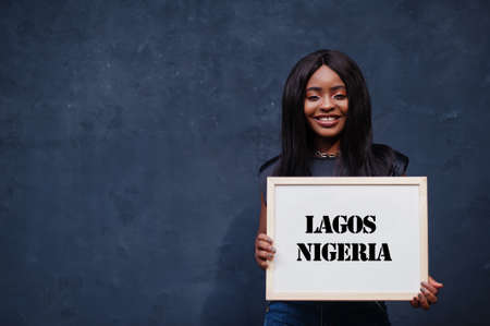African woman hold white board with Lagos Nigeria inscription. Most populous city in Africa concept. Imagens