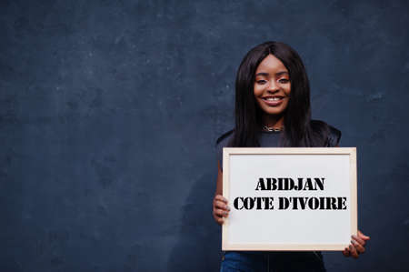 African woman hold white board with Abidjan Cote d'Ivoire inscription. Most populous city in Africa concept.
