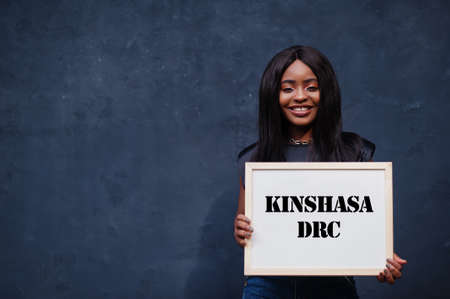 African woman hold white board with Kinshasa DRC inscription. Most populous city in Africa concept.