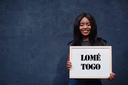 African woman hold white board with Lome Togo inscription. Most populous city in Africa concept. Imagens