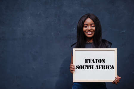 African woman hold white board with Evaton South Africa inscription. Most populous city in Africa concept.