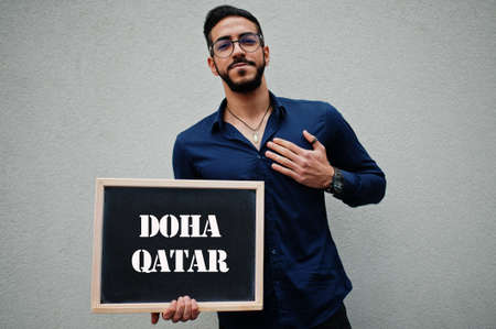 Arab man wear blue shirt and eyeglasses hold board with Doha Qatar inscription. Largest cities in islamic world concept.