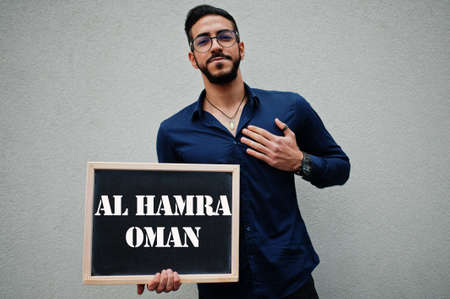 Arab man wear blue shirt and eyeglasses hold board with Al Hamra Oman inscription. Largest cities in islamic world concept.