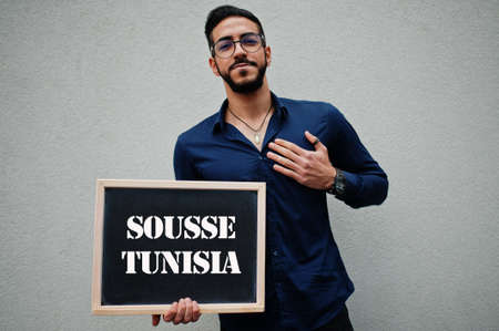 Arab man wear blue shirt and eyeglasses hold board with Sousse Tunisia inscription. Largest cities in islamic world concept.