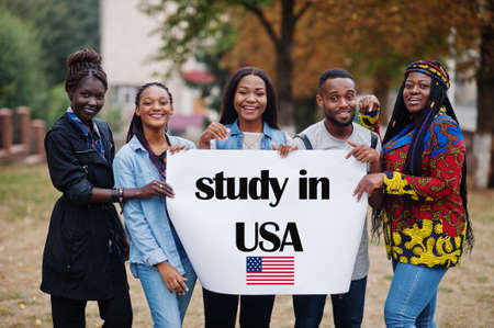 Study in USA. Group of five african college students on campus at university yard hold white blank. Abroad countries for student concept.
