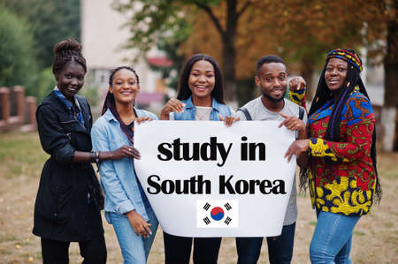 Study in South Korea. Group of five african college students on campus at university yard hold white blank. Abroad countries for student concept.