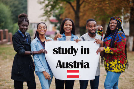 Study in Austria. Group of five african college students on campus at university yard hold white blank. Abroad countries for student concept.
