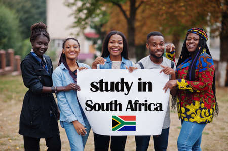 Study in South Africa. Group of five african college students on campus at university yard hold white blank. Abroad countries for student concept.