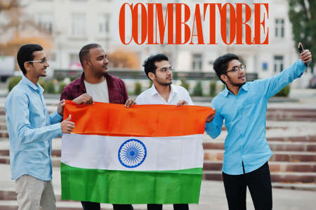 Coimbatore city inscription. Group of four indian male friends with India flag making selfie on mobile phone. Largest India cities concept.