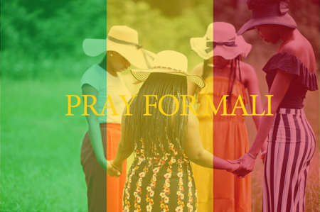Pray for Mali. Group of four african women holding hands and praying. Concept of crisis in Africa country.