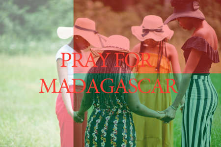 Pray for Madagascar. Group of four african women holding hands and praying. Concept of crisis in Africa country.
