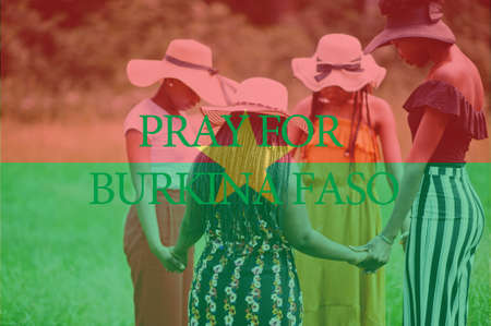 Pray for Burkina Faso. Group of four african women holding hands and praying. Concept of crisis in Africa country.