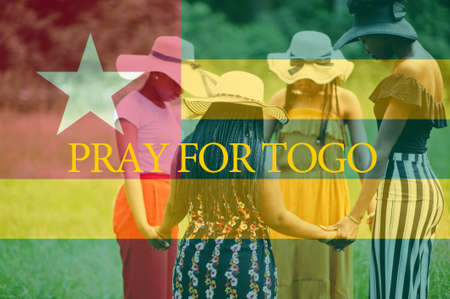 Pray for Togo. Group of four african women holding hands and praying. Concept of crisis in Africa country.