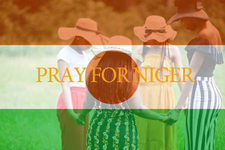 Pray for Niger. Group of four african women holding hands and praying. Concept of crisis in Africa country.