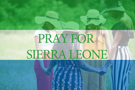 Pray for Sierra Leone. Group of four african women holding hands and praying. Concept of crisis in Africa country.