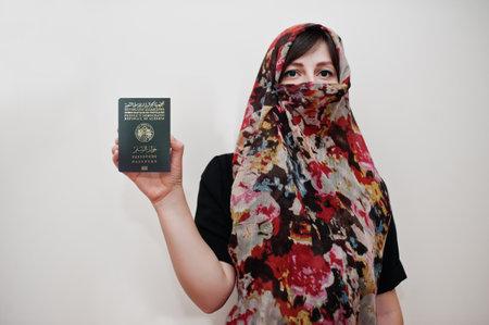 Young arabian muslim woman in hijab clothes hold People's Democratic Republic of Algeria passport on white wall background, studio portrait. Zdjęcie Seryjne