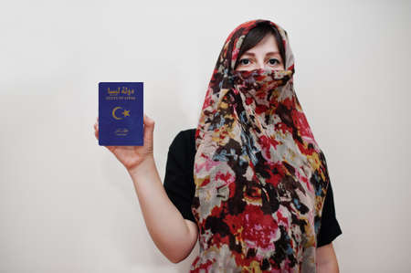 Young arabian muslim woman in hijab clothes hold State of Libya passport on white wall background, studio portrait. Archivio Fotografico