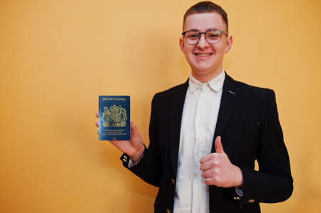 Young handsome man holding United Kingdom of Great Britain and Northern Ireland passport id over yellow background, happy and show thumb up. Travel to Europe country concept.