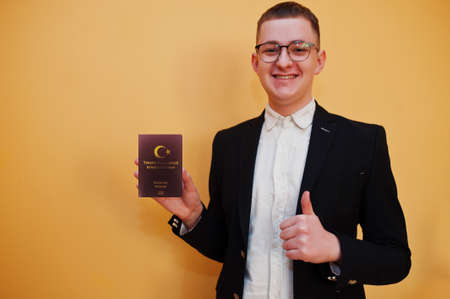 Young handsome man holding Republic of Turkey passport id over yellow background, happy and show thumb up. Travel to Europe country concept.