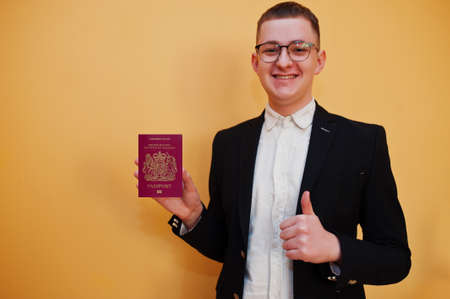 Young handsome man holding Bailiwick of Guernsey passport id over yellow background, happy and show thumb up. Travel to Europe country concept.