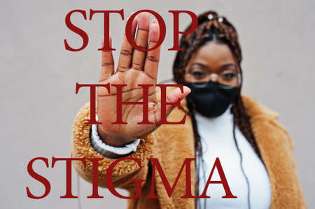 Stop the stigma. African american woman, wear black face mask show stop hand sign. Stock Photo