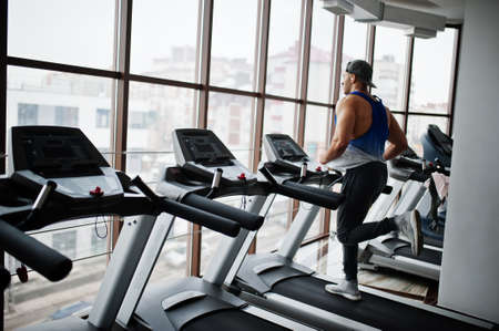 Fit and muscular arabian man running on treadmill in gym.