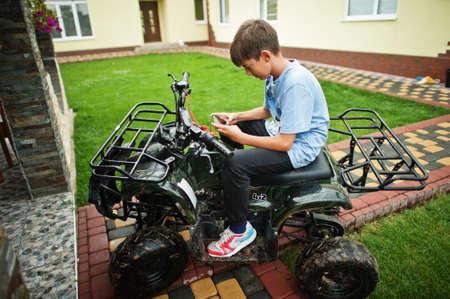 Boy in four-wheller ATV quad bike with mobile phone. Reklamní fotografie