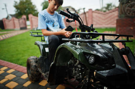 Boy in four-wheller ATV quad bike with mobile phone.