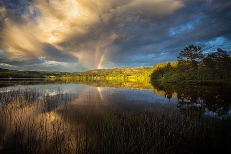 Triple rainbow observed above Jonsvatnet lake near Trondheim, sunset light after stormy day, summer in Norway. 版權商用圖片