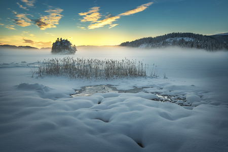 Frozen lake Jonsvatnet near Trondheim, Norway. Sunset light over gathering fog. Banque d'images