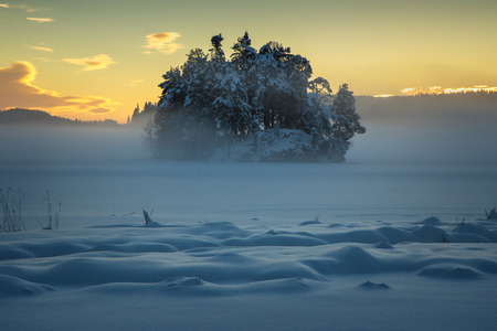 Frozen lake Jonsvatnet near Trondheim, Norway. Sunset light over gathering fog. Stock fotó