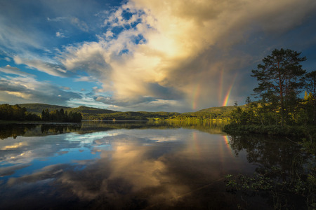 riple rainbow observed above Jonsvatnet lake near Trondheim, sunset light after stormy day, summer in Norway.