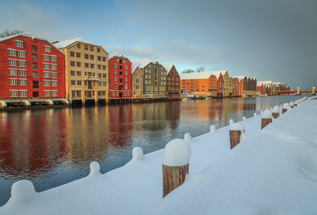 Old wooden buildings, magazines, by the shores of Nidelva river, winter time in Trondheim, Norway. Stok Fotoğraf