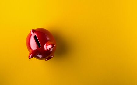 Red piggy bank on yellow background Фото со стока