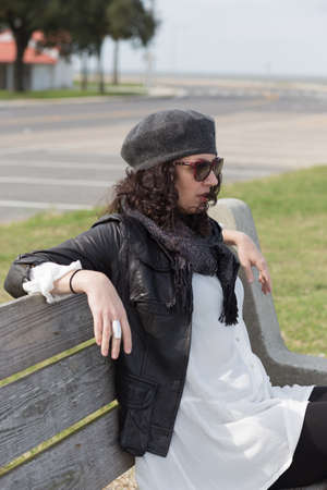generation x: Profile of woman in sunglasses and grey beret sitting on wooden park bench Stock Photo
