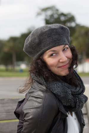 knowing: Portrait of woman with grey beret, dark scarf and knowing smile Stock Photo