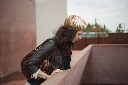 ledge: Woman with gold sequin beret shining in the sun, looking over rusty red concrete ledge at dock