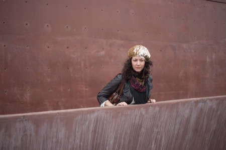 generation x: Woman looking over ledge with rusty red concrete wall