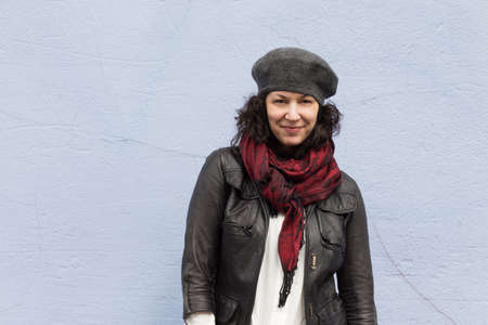 thirtysomething: Smiling woman bundled up in stylish clothes for winter, in front of blue background
