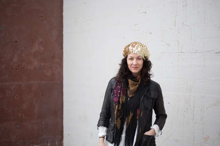thirtysomething: Woman with curly brown hair wearing urban bohemian fashion  white and red wall sections