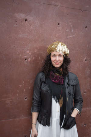 facing to camera: Portrait of curly-haired brunette, wearing bohemian gypsy style clothing, facing camera with marsala red concrete background wall