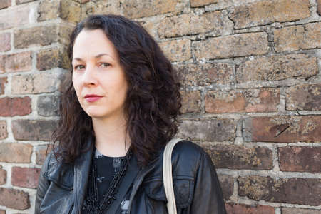 gen: Serious woman with dark curly hair and black clothes in front of old brick wall Stock Photo