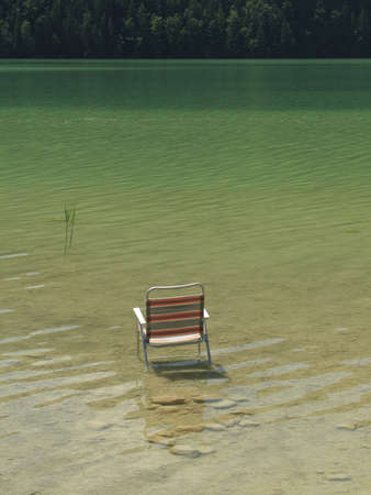 water's edge: Folding Chair in the Water Stock Photo