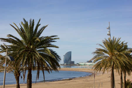 Barcelona, Spain, 03 May 2020: a sunny day view of the empty and closed Barcelona beach with palm trees in the foreground and the hotel W on the background. One of the beaches of the Mediterranean coast