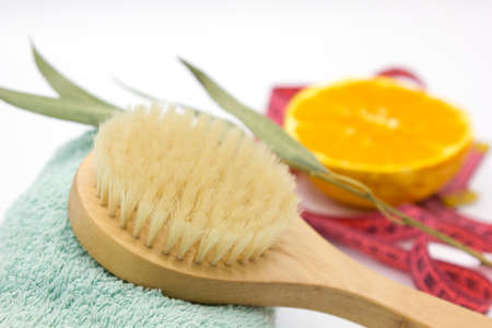 Spa organic brush for dry massage on towel, orange, sprig of eucalyptus and a tape measure on white background. Cactus brush. Anti-cellulite massage. Spa beauty concept.Close up