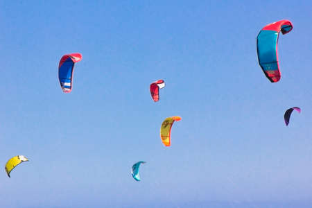 Kite-surfing against a beautiful blue sky. Many silhouettes of kites in the sky. Travel concept. Beauty world. watersports. Wind lovers. Type of kite. Kite course Stock Photo