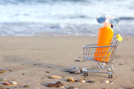 An orange sunscreen locion bottle in mini shopping trolley or cart with round vintage sunglasses with sky and clouds on the beach with sea background. Space for text. Skin care concept. Sun protection Foto de archivo