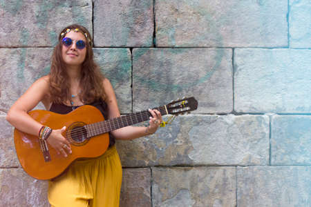 Beautiful curly hair brunette hippie girl with vintage blue sunglasses and guitar sitting on a square. Street music and free lifestyle concept. Foto de archivo