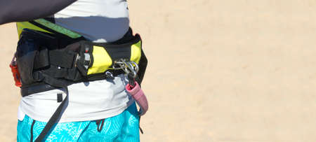 torso of a man on the beach with arnes (harness) for kitesurfing at the waist. Extreme Water Sports and kiteboarding equipment