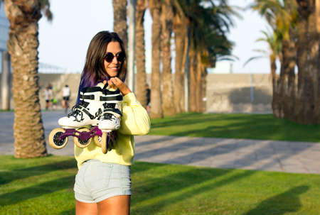 young beautiful fit girl with blue hair and sunglasses standing on grass in park, turning around from the back, smiling and holding rollers on shoulder. sporty roller skates lifestyle. joys of life